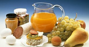Mug with juice, fruit, sausage, eggs and tartlet